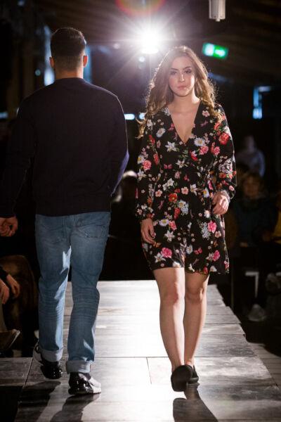 Modevisning, flicka i blommig klänning går på catwalken